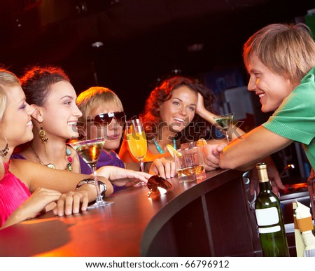 Image of happy teenagers holding the cocktails and chatting
