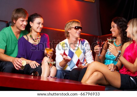 Image of happy teenagers holding the cocktails and chatting - stock photo
