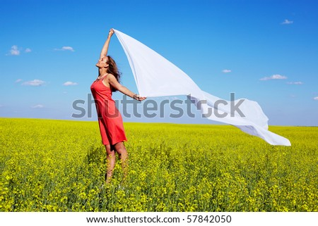 Image of happy woman holding a white fabric in the yellow meadow - stock photo