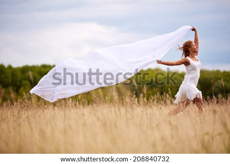 Image of happy woman with white fabric running down meadow - stock photo