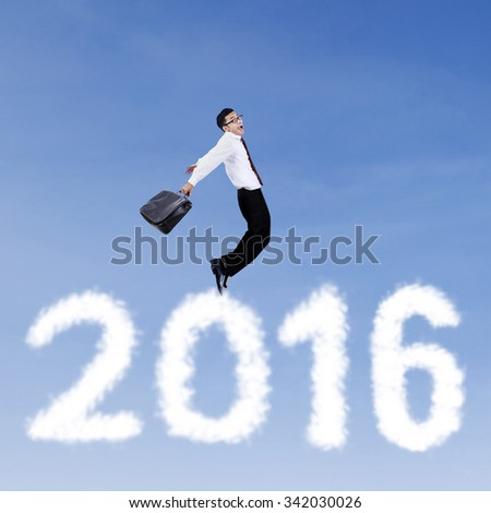 Image of happy young businessman jumping on the sky above clouds shaped numbers 2016 - stock photo