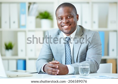Image of happy young businessman looking at camera at workplace - stock photo