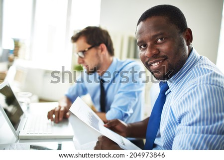 Image of happy young businessmen looking at camera on background of his colleague using laptop - stock photo
