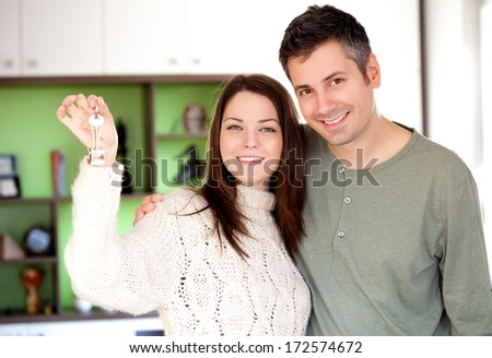 Image of happy young couple smiling and holding key ring - stock photo