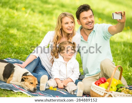 Image of happy young family having picnic outdoors and making selfie. - stock photo