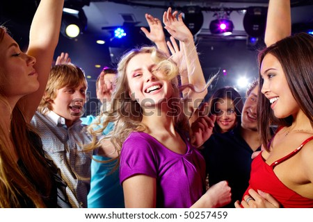 Image of happy young girls having fun at disco - stock photo