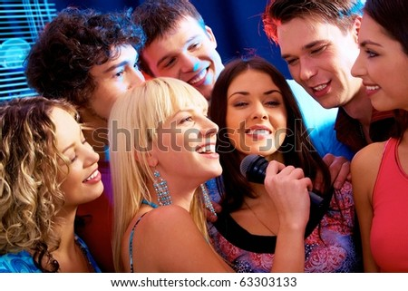 Image of happy young woman sings a song in the environment of her friends - stock photo