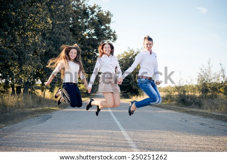 Image of 3 happy young women jumping on the countryside road on summer blue sky background - stock photo