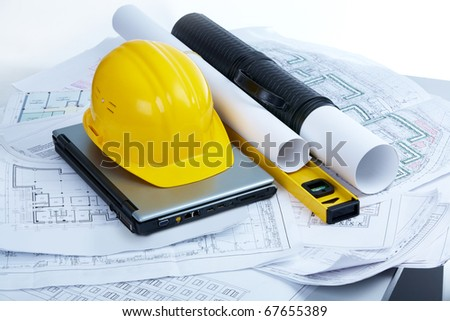 Image of helmet, blueprints, laptop and mechanical tools at workplace - stock photo