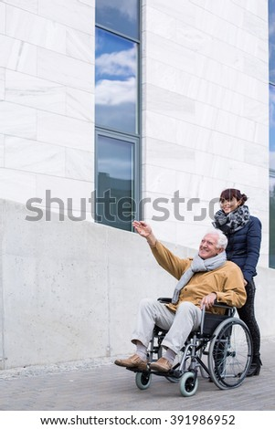 Image of helpful female spending time with grandfather outdoors - stock photo