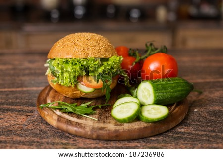 Image of home made vegetables burger with tomatoes on branch and slices of cucumber on wooden board - stock photo