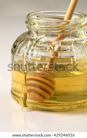 image of honey and wooden dipper in a glass - stock photo