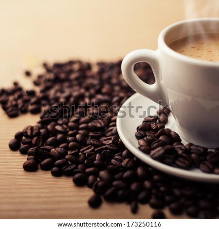 image of hot coffee drink, with coffee beans around plate and on plate.  - stock photo