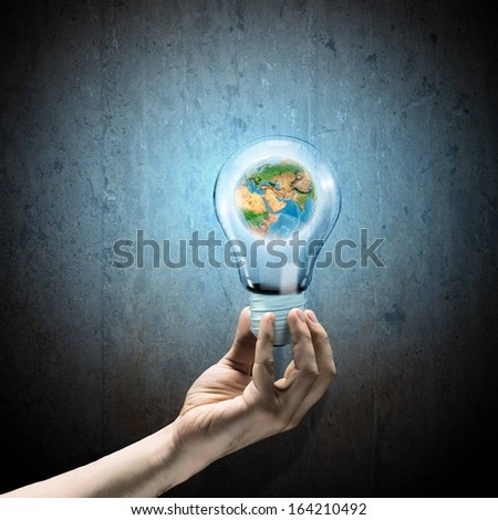 Image of human hand holding bulb with earth planet inside. Elements of this image are furnished by NASA - stock photo