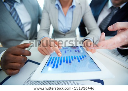 Image of human hands during discussion of business document in touchscreen at meeting - stock photo