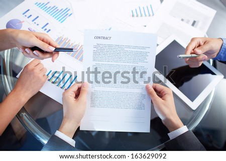 Image of human hands during discussion of contract at meeting  - stock photo