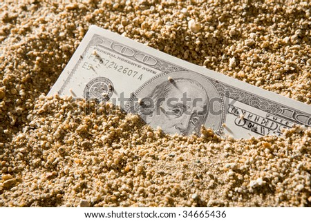 Image of hundred dollar banknote in sand - stock photo
