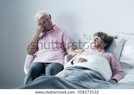 Image of husband supporting mortally ill old wife - stock photo