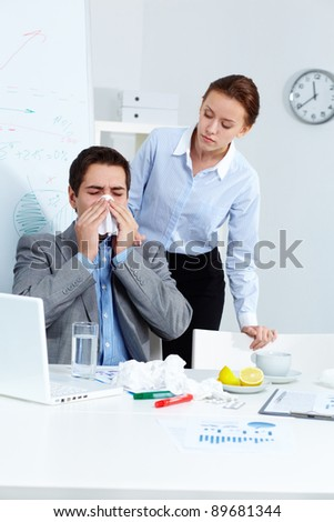 Image of ill businessman sneezing while his partner looking at him with care in office - stock photo