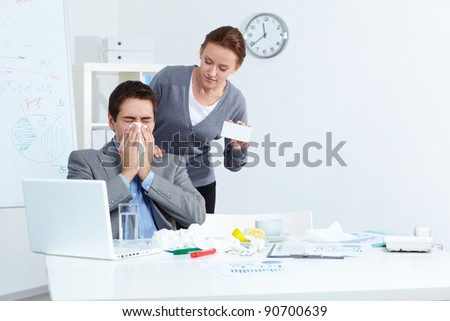 Image of ill businessman sneezing while his partner offering him good medicine in office - stock photo