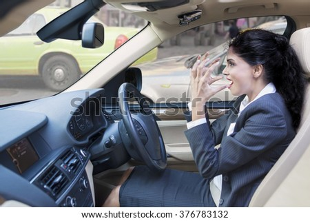 Image of indian young businesswoman looks angry while driving her car on the road - stock photo
