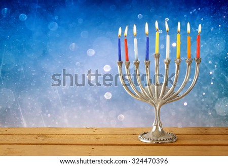 Image of jewish holiday Hanukkah background with menorah (traditional candelabra) and Burning candles with glitter background  - stock photo