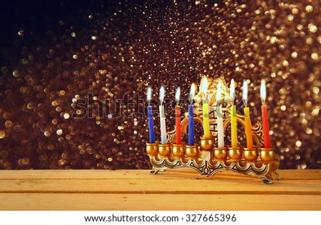 Image of jewish holiday Hanukkah background with menorah (traditional candelabra) Burning candles over black background and glitter lights  - stock photo
