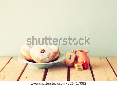 image of jewish holiday Hanukkah with  donuts and wooden dreidels (spinning top). retro filtered - stock photo