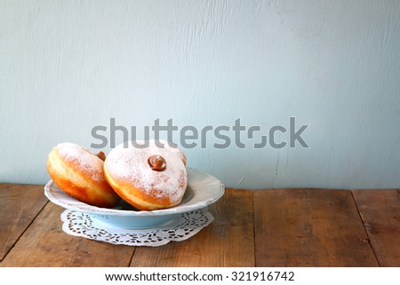 image of jewish holiday Hanukkah with donuts on wooden table  - stock photo