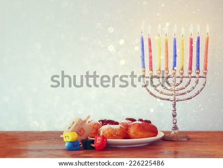 Image of jewish holiday Hanukkah with menorah, doughnuts and wooden dreidels (spinning top). retro filtered image  - stock photo