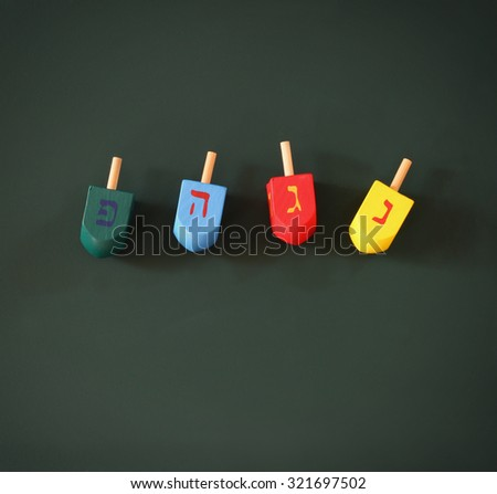 image of jewish holiday Hanukkah with wooden colorful dreidels (spinning top) over chalkboard background. room for text  - stock photo