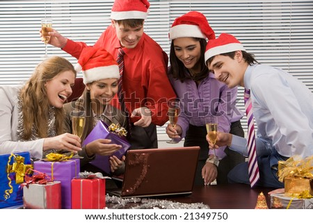Image of joyful business group looking at screen of laptop and reading greets with smiles - stock photo