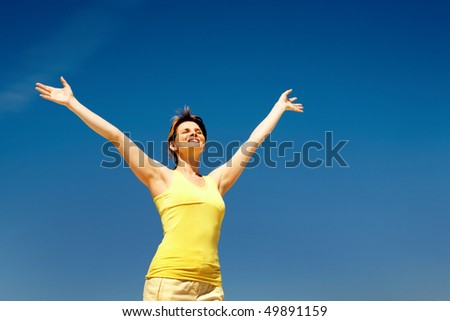 Image of joyful female in casual clothes enjoying herself against blue sky - stock photo