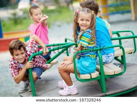 Image of joyful friends having fun on carousel outdoors  - stock photo
