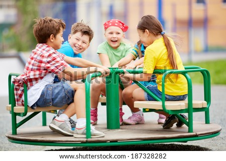 Image of joyful friends having fun on carousel outdoors  - stock photo