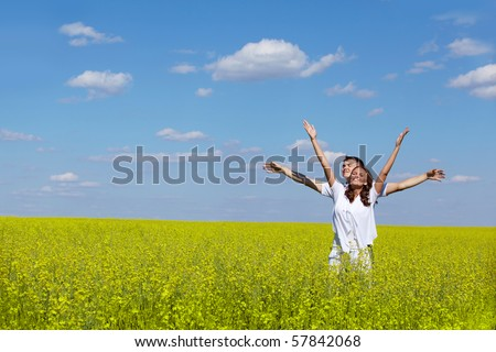 Image of joyful girl and her boyfriend standing in yellow meadow with raised arms