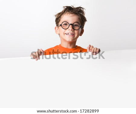 Image of joyful guy in glasses holding white partition and looking at camera with smile - stock photo