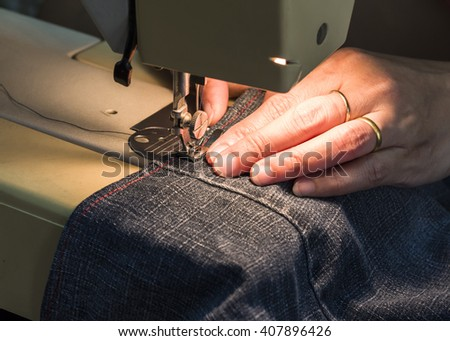 image of lady  hands sewing her cloth with the light of sewing machine, close up
