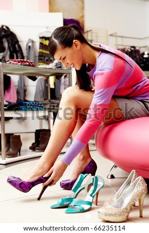 Image of lady trying on several pairs of new shoes in the mall - stock photo