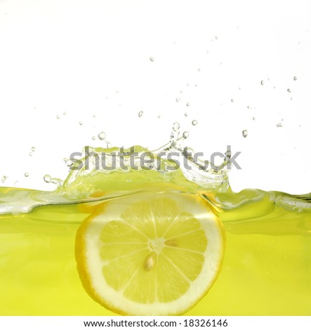 Image of lemon slice falling into juice - stock photo