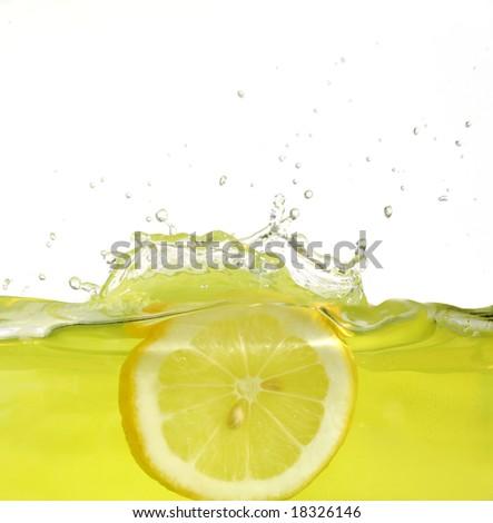 Image of lemon slice falling into juice - stock photo