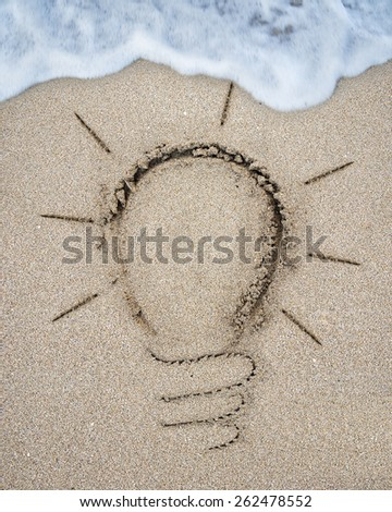 Image of light bulb drawn on the sand beach with white wave foam background - stock photo