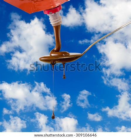 image of  liquid chocolate on a spoon against the sky - stock photo