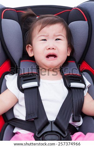 Image of little asian (thai) girl crying and fastened with security belt in safety car-seat. Concept about the safety of traveling by car, children and baby - stock photo