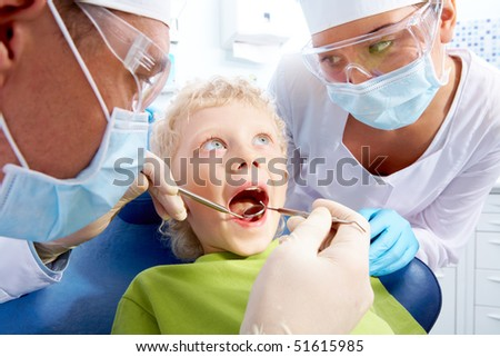 Image of little boy having teeth checked by doctor and assistant - stock photo