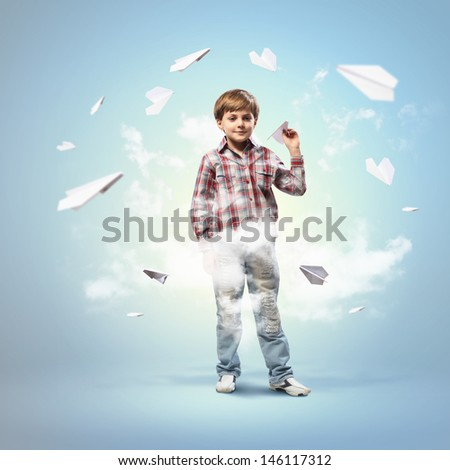 Image of little boy playing with paper airplane against blue background - stock photo