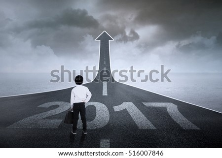 Image of little businessman with a briefcase standing on a road with number 2017 and upward arrow