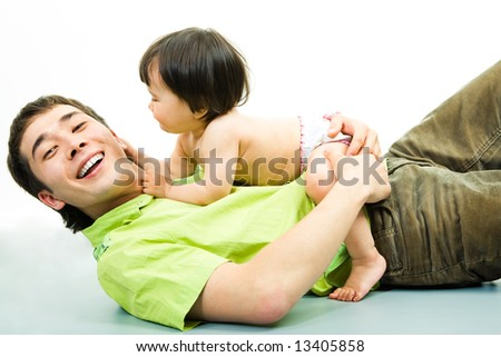 Image of little girl  lying over his daddy and touching him - stock photo