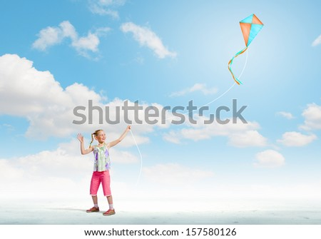 Image of little girl playing with kite at meadow