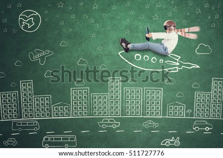 Image of little kid riding rocket picture and doodles on the chalkboard while imagining fly in the city
